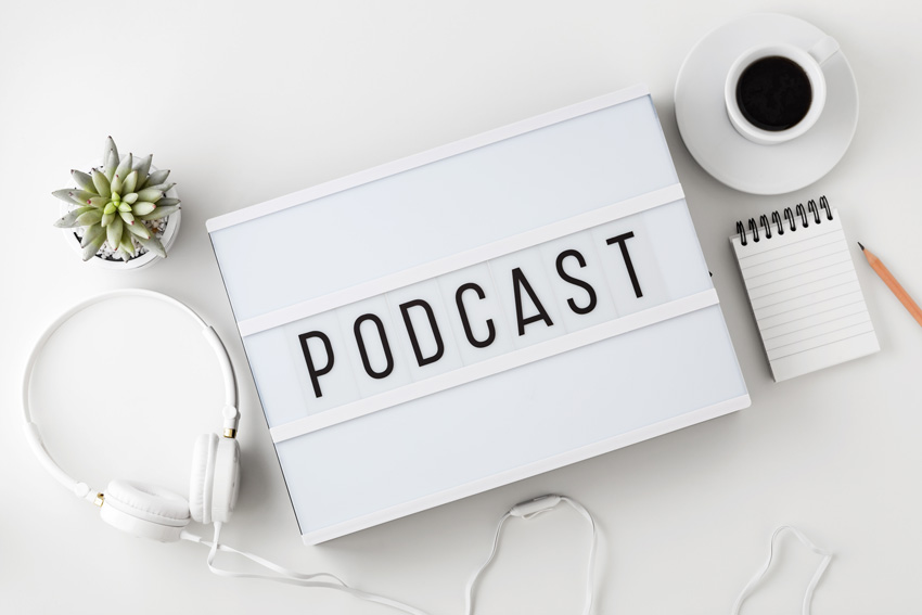 Podcast word on lightbox with headphones on white table, flat lay